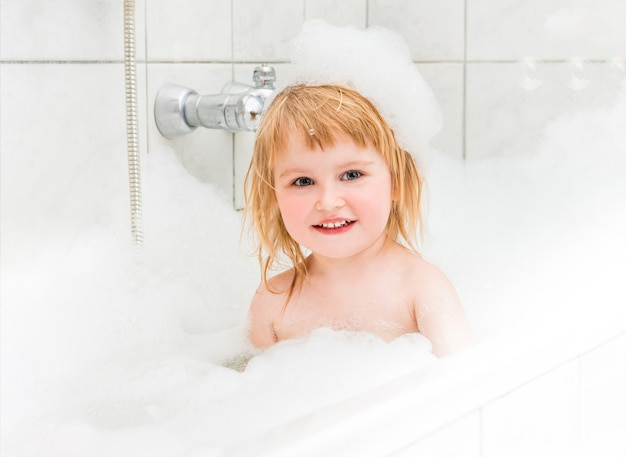 Kleines mädchen badet in einem bad mit schaum und luftblasen Premium Fotos