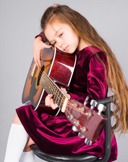Kleines mädchen, das akustikgitarre auf stuhl spielt Kostenlose Fotos