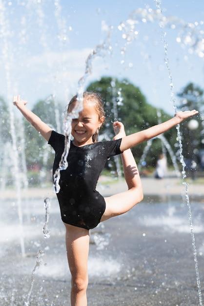 Kleines mädchen, das am wasserbrunnen spielt Kostenlose Fotos