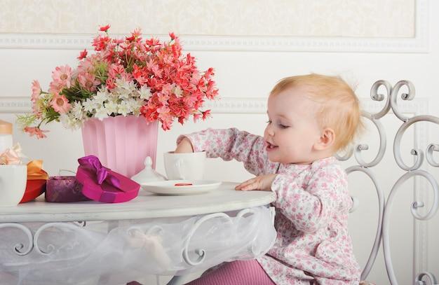 Kleines mädchen, das an einem tisch mit tee und dekorationen, porträt, nahaufnahme sitzt Premium Fotos