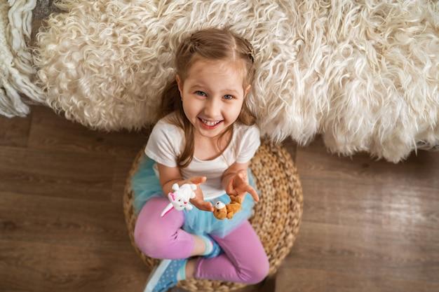 Kleines mädchen, das auf boden sitzt, der auf sofa lehnt und spaß spielt mit fingerspielzeug Premium Fotos