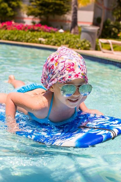 Kleines mädchen, das auf einem surfbrett im swimmingpoll schwimmt Premium Fotos