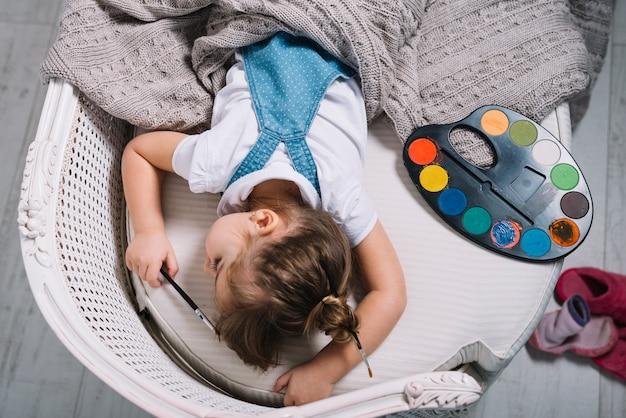 Kleines mädchen, das auf sofa mit aquarellpalette schläft Kostenlose Fotos