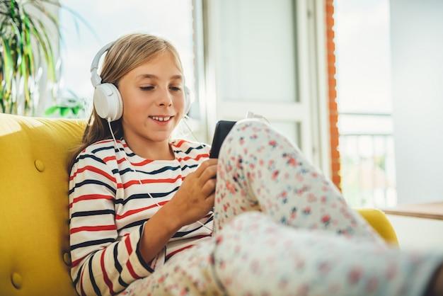 Kleines mädchen, das auf sofa sitzt und intelligentes telefon verwendet Premium Fotos