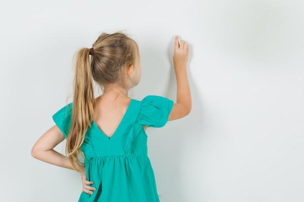 Kleines mädchen, das auf wand mit finger in der ansicht des grünen kleides zurück zeichnet. Kostenlose Fotos