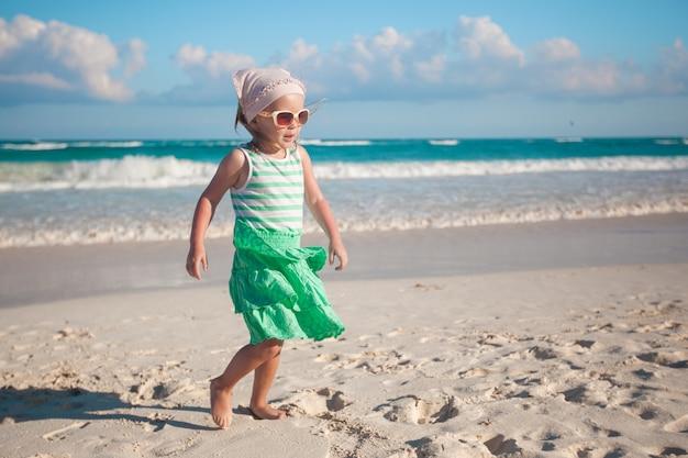 Kleines mädchen, das auf weißen sandigen strand in mexiko geht Premium Fotos