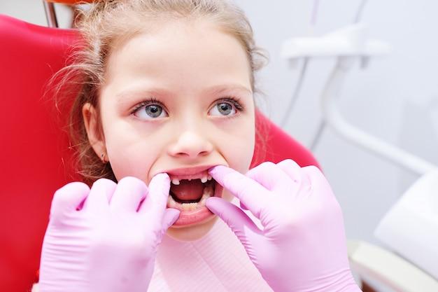 Kleines mädchen, das auf zahnmedizinischem stuhl im büro der pädiatrischen zahnärzte sitzt. Premium Fotos
