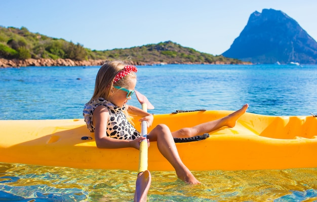Kleines mädchen, das das schwimmen im gelben kajak im klaren türkiswasser genießt Premium Fotos