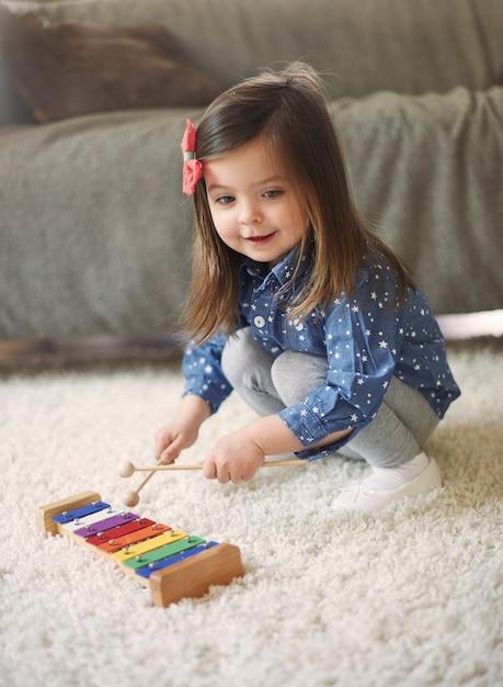 Kleines mädchen, das das xylophon spielt Kostenlose Fotos