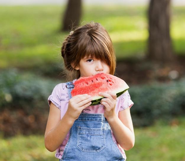 Kleines mädchen, das draußen wassermelonenscheibe genießt Kostenlose Fotos