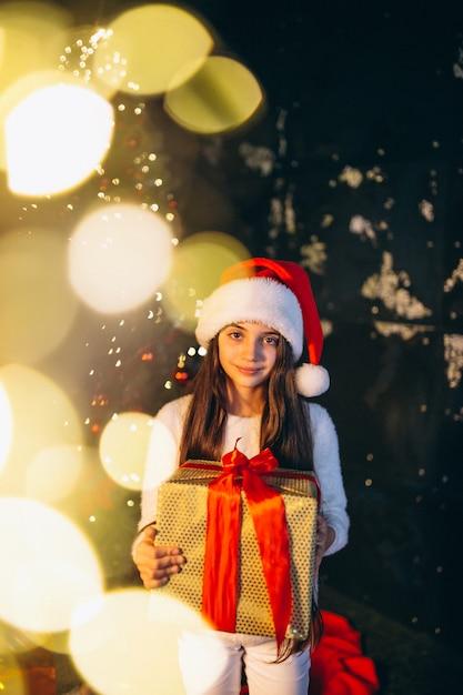 Kleines mädchen, das durch weihnachtsbaum sitzt und geschenke auspackt Kostenlose Fotos