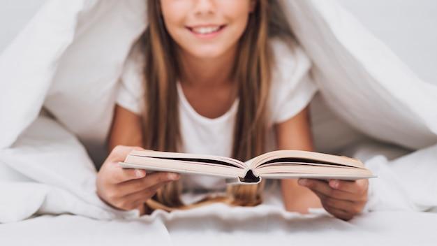 Kleines mädchen, das ein buch im bett liest Kostenlose Fotos