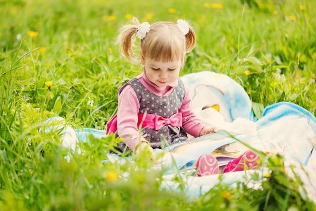 Kleines mädchen, das ein buch im sommerpark liest Premium Fotos