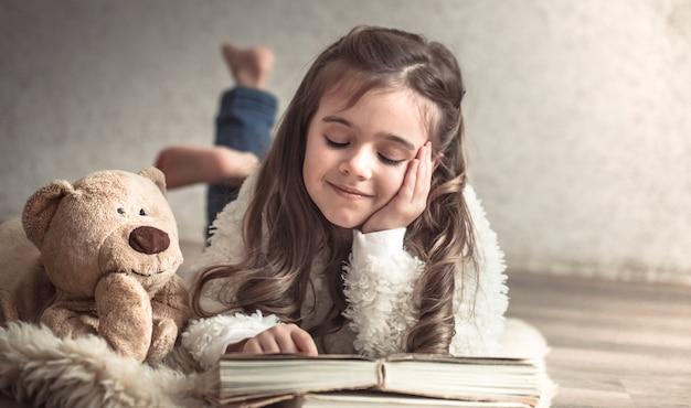 Kleines mädchen, das ein buch mit einem teddybär auf dem boden liest, konzept der entspannung und der freundschaft Kostenlose Fotos
