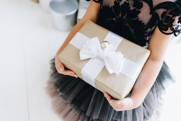 Kleines mädchen, das ein eingewickeltes weihnachtsgeschenk hält Premium Fotos