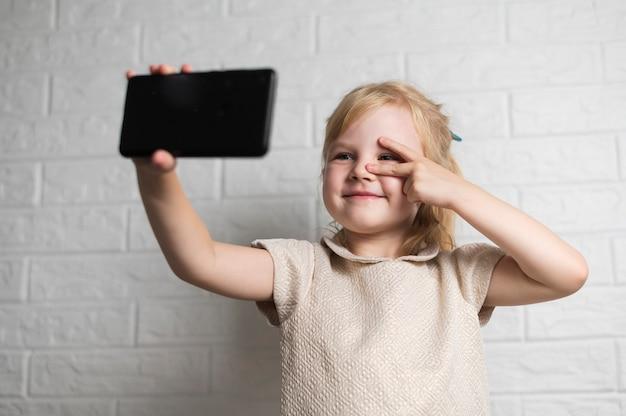 Kleines mädchen, das ein selfie nimmt Kostenlose Fotos