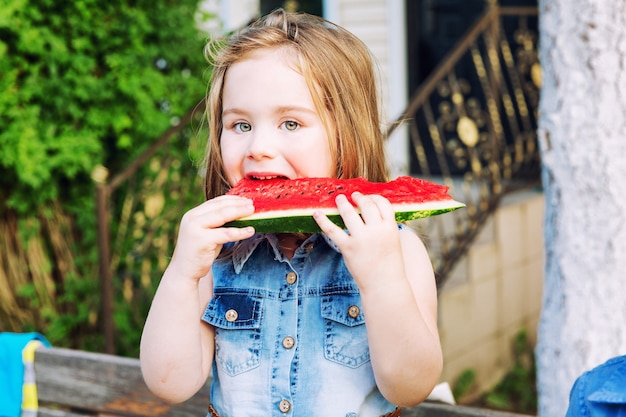 Kleines mädchen, das eine wassermelone im garten isst Premium Fotos