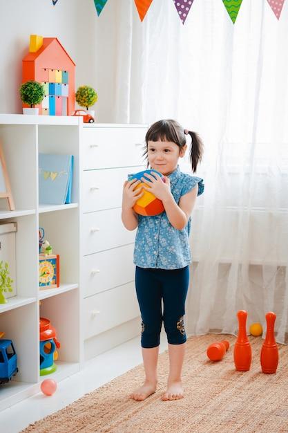 Kleines mädchen, das einen ball im spielzimmer hält. Premium Fotos