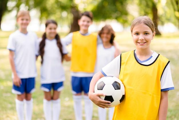 Kleines mädchen, das einen fußball neben ihren teamkollegen hält Premium Fotos