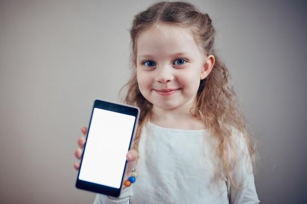 Kleines mädchen, das einen smartphone mit einem weißen schirm hält Premium Fotos