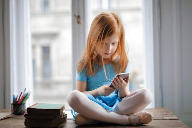Kleines mädchen, das einen smartphone verwendet Premium Fotos