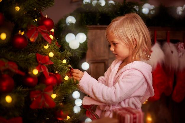 Kleines mädchen, das einen weihnachtsbaum verziert Kostenlose Fotos