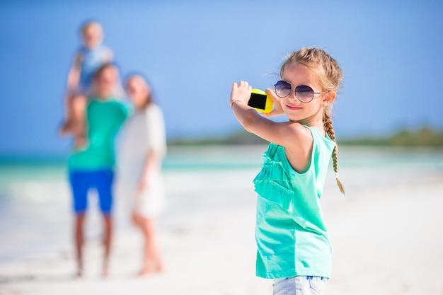 Kleines mädchen, das foto am telefon von der familie am strand macht Premium Fotos