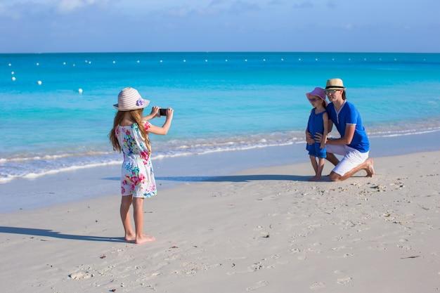 Kleines mädchen, das foto am telefon von ihrer familie am strand macht Premium Fotos