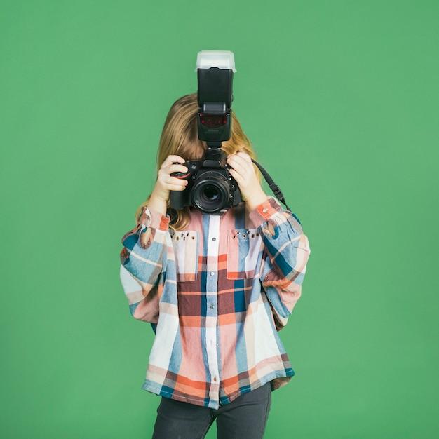 Kleines mädchen, das foto mit kamera macht Kostenlose Fotos