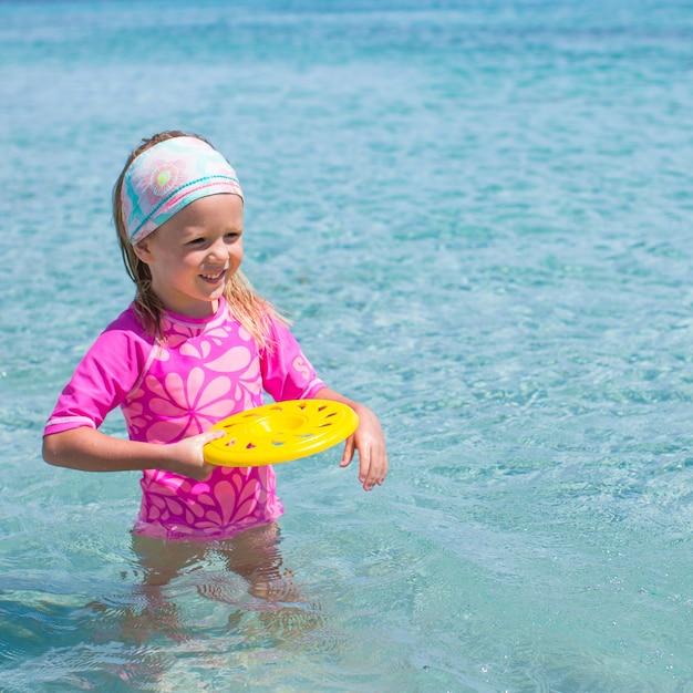 Kleines mädchen, das frisbee während der tropischen ferien im meer spielt Premium Fotos