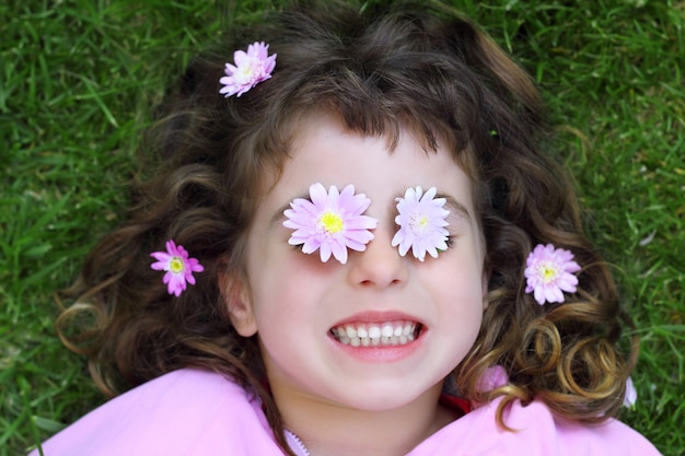 Kleines mädchen, das gras daisiy blumen in augen legt Premium Fotos