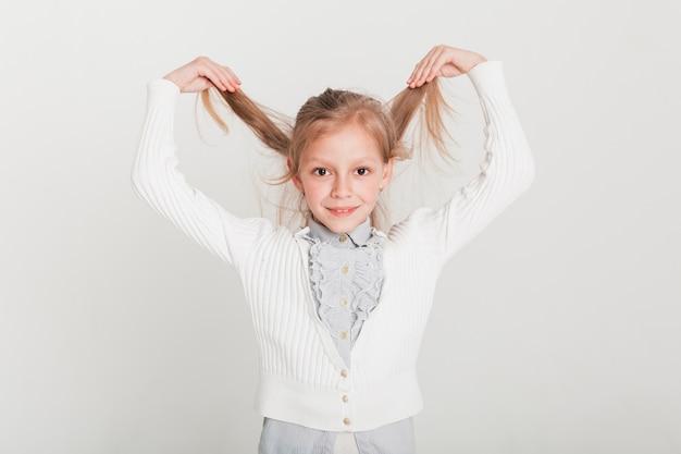 Kleines mädchen, das ihre haare anhebt Kostenlose Fotos