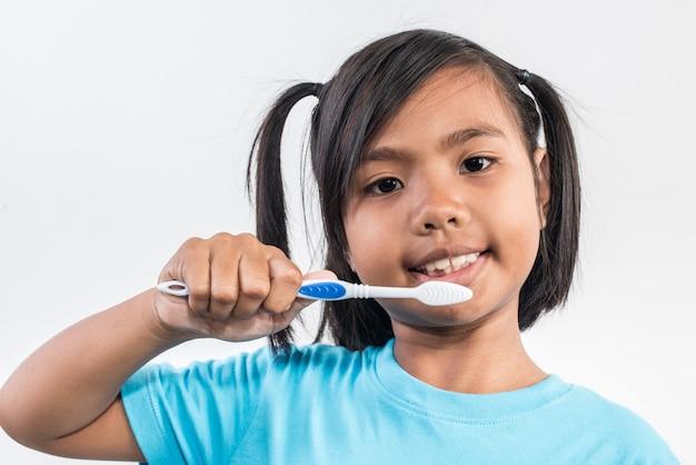 Kleines mädchen, das ihre zähne in der atelieraufnahme putzt Kostenlose Fotos