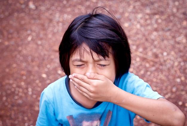 Kleines mädchen, das ihren mund mit ihrer hand bedeckt. Premium Fotos