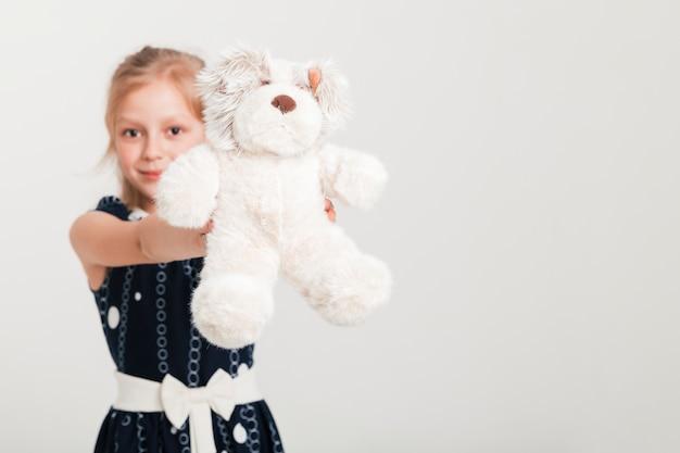 Kleines mädchen, das ihren teddybären zeigt Kostenlose Fotos