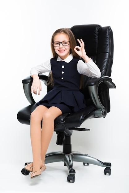 Kleines mädchen, das im stuhl zeigt das okayzeichen gekleidet als geschäftsfrau sitzt Premium Fotos