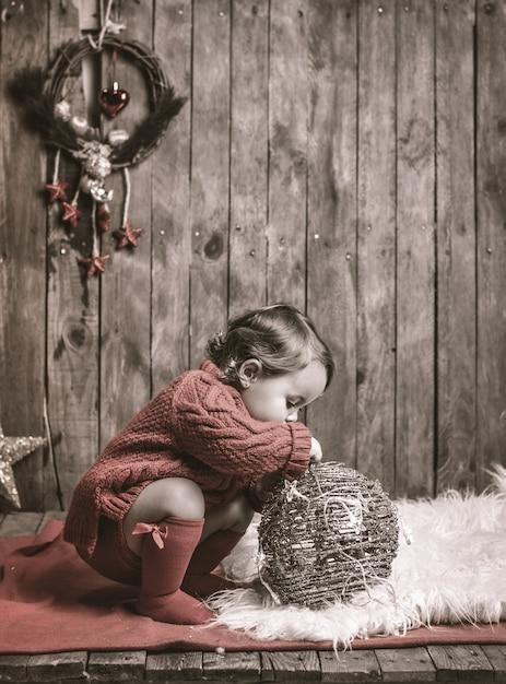Kleines mädchen, das in der weihnachtsdekoration spielt. Premium Fotos