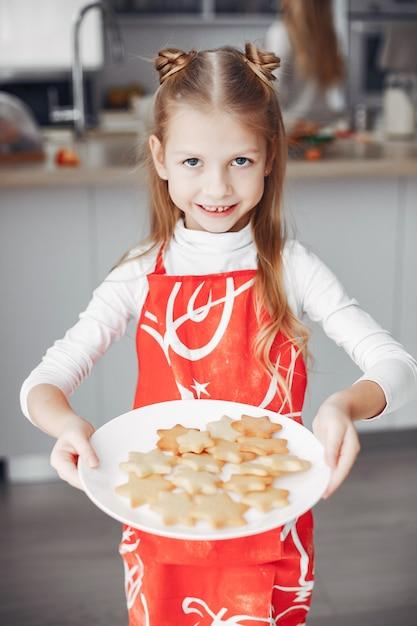 Kleines mädchen, das in einer küche mit plätzchen steht Kostenlose Fotos