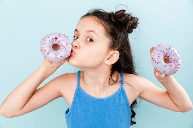 Kleines mädchen, das köstlichen donut küsst Kostenlose Fotos