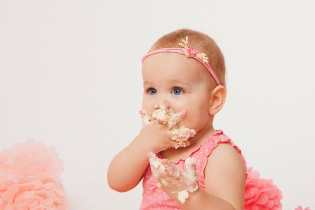 Kleines mädchen, das kuchen mit ihren händen auf weiß isst Premium Fotos