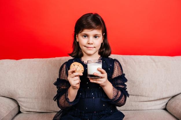 Kleines mädchen, das milch auf roter wand trinkt. innenaufnahme des kindes, das keks isst. Kostenlose Fotos
