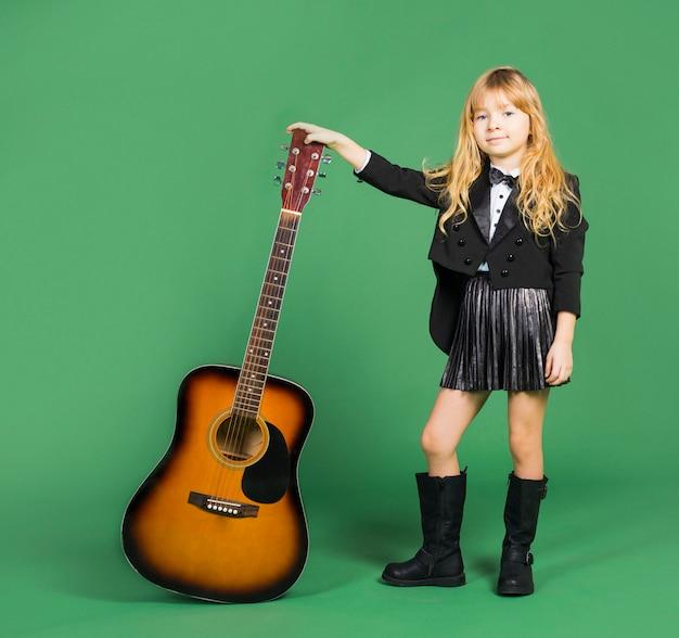 Kleines mädchen, das mit akustikgitarre steht Kostenlose Fotos