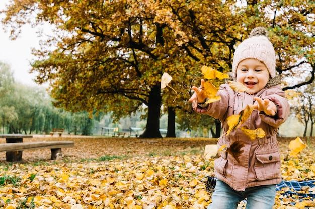 Kleines mädchen, das mit herbstblättern im park spielt Kostenlose Fotos