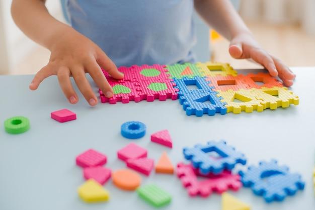 Kleines mädchen, das mit puzzlespiel, früherziehung spielt Premium Fotos