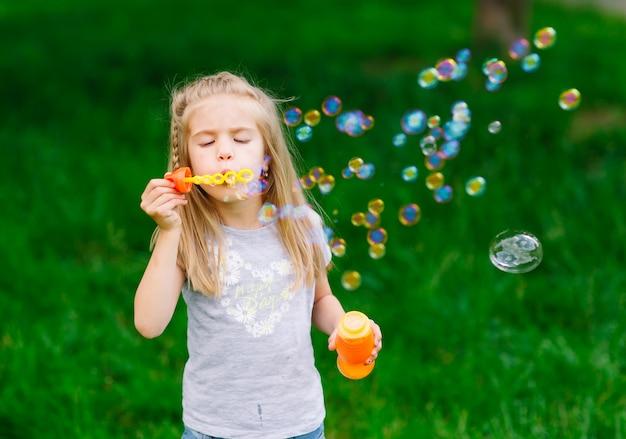 Kleines mädchen, das mit seifenblasen spielt. Premium Fotos