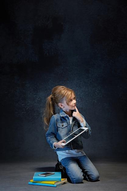 Kleines mädchen, das mit tablette im grauen studio sitzt Kostenlose Fotos