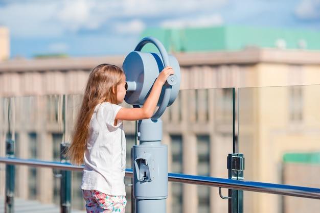 Kleines mädchen, das münzbetriebenes fernglas auf terrasse mit schöner ansicht betrachtet Premium Fotos