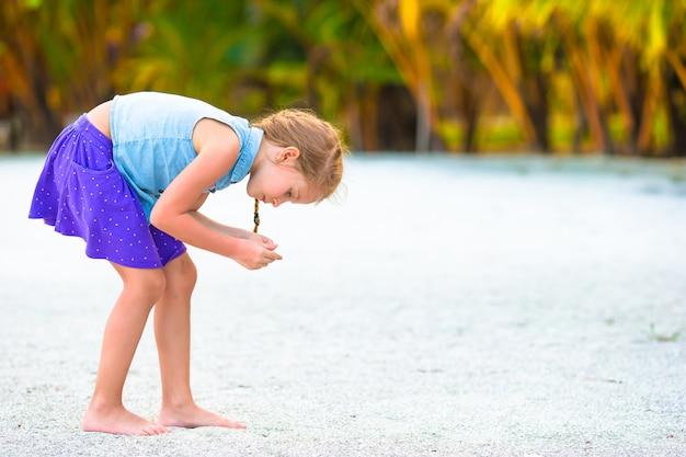Kleines mädchen, das muscheln auf weißem sandstrand sammelt Premium Fotos