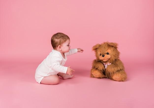 Kleines mädchen, das neben einem plüschtierhund kriecht Premium Fotos