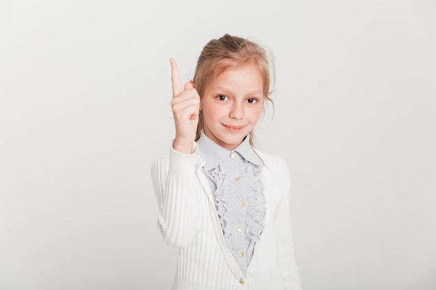 Kleines mädchen, das oben mit dem finger zeigt Kostenlose Fotos